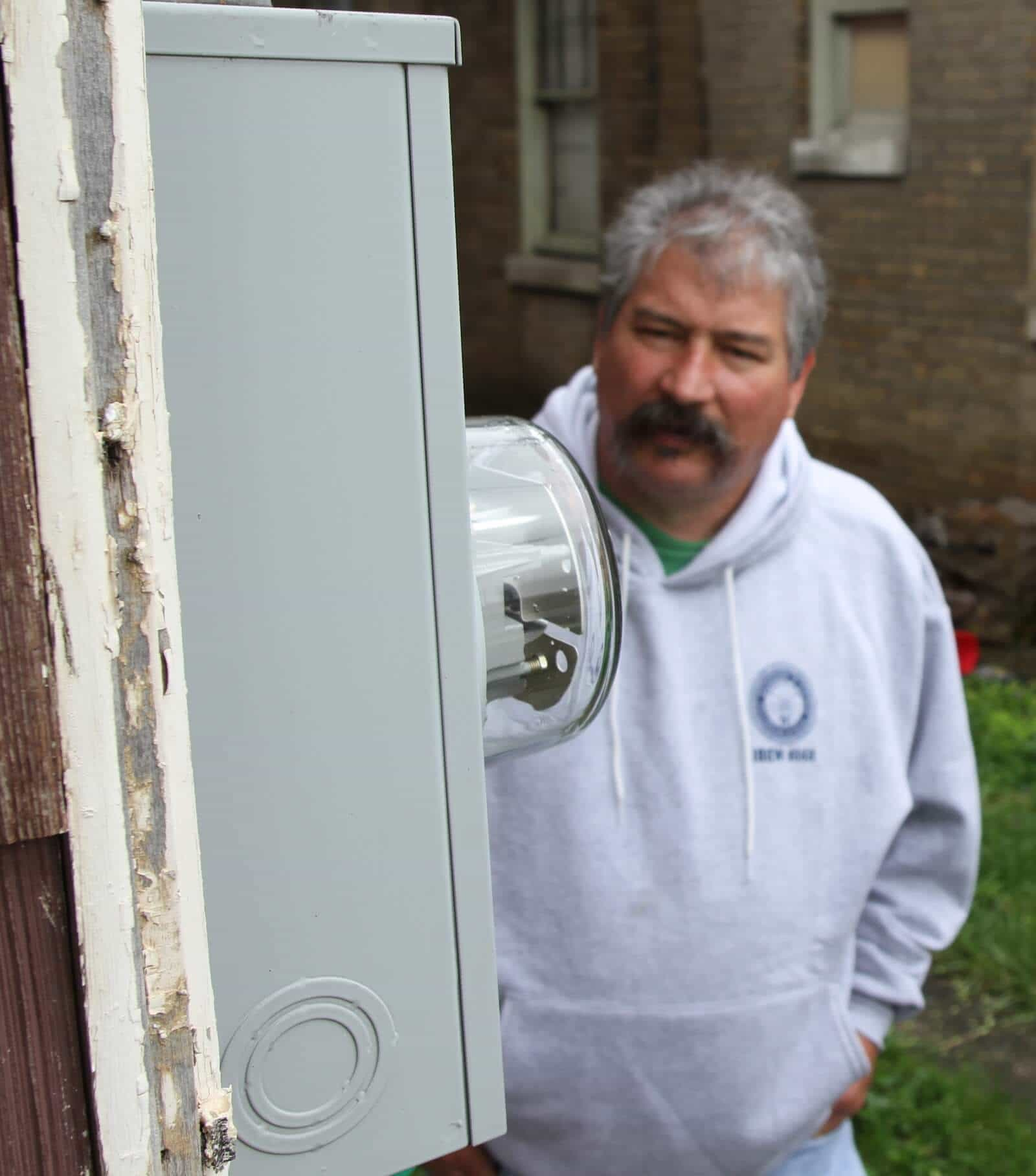 Larry Spencer inspects meter on Habitat build project